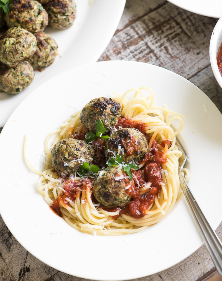 A plate of zucchini beef meatballs on pasta with marinara sauce
