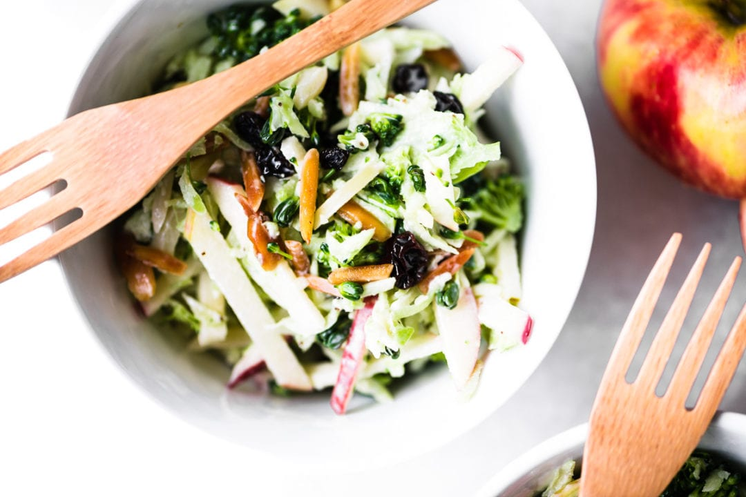 Broccoli Honeycrisp Slaw in a small white bowl with a bamboo fork
