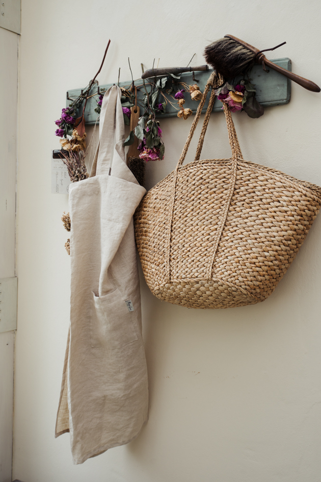 straw market tote hanging on a peg board