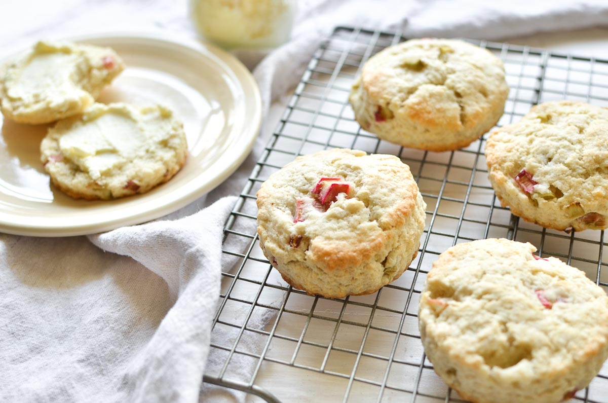 Rhubarb scones on a cooling rack, with a split scone spread with clotted cream