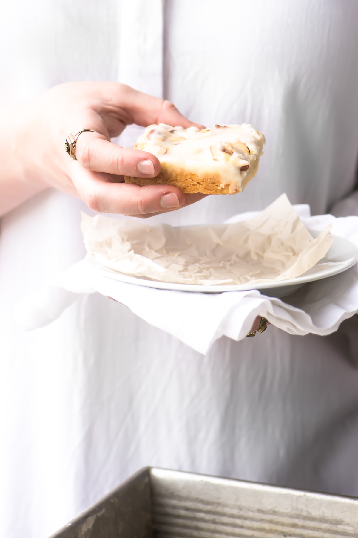 Holding an almond shortbread bar with a plate and napkin