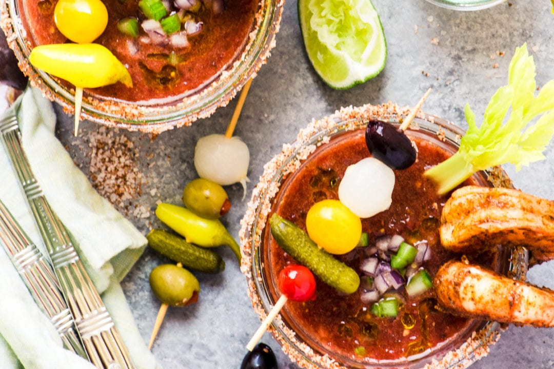 Bloody Mary Gazpacho with lime wedges and garnishes