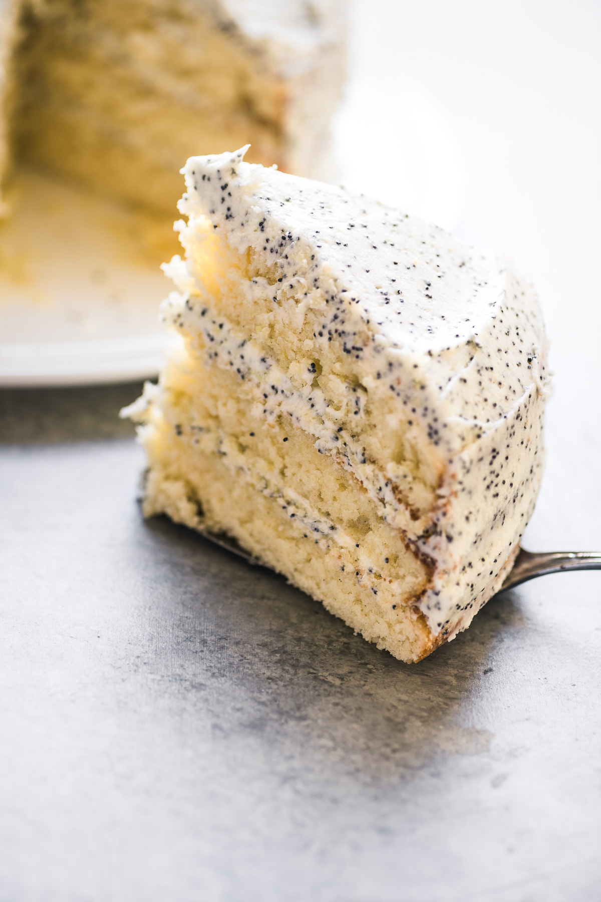 a slice of lemon layer cake with lemon poppy seed buttercream