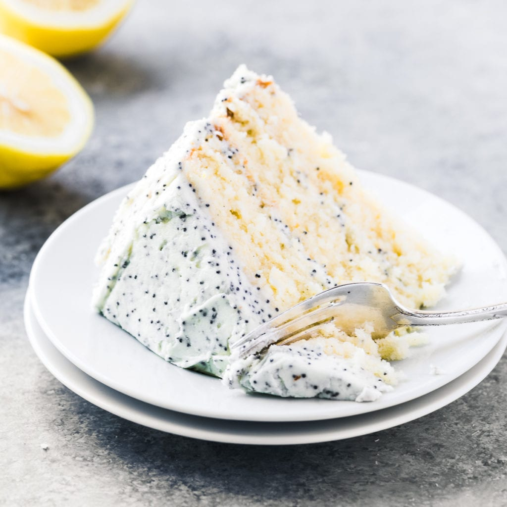 a slice of lemon layer cake with lemon poppy seed frosting