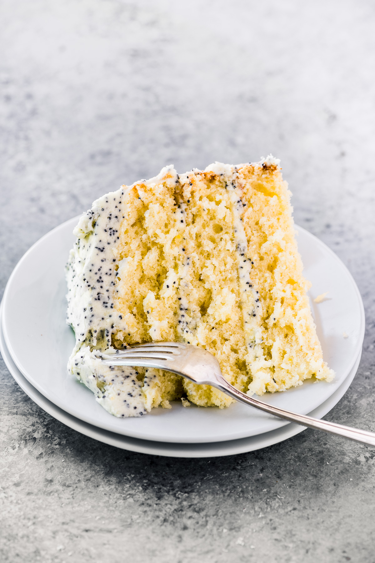 a slice of lemon layer cake on a plate with fork
