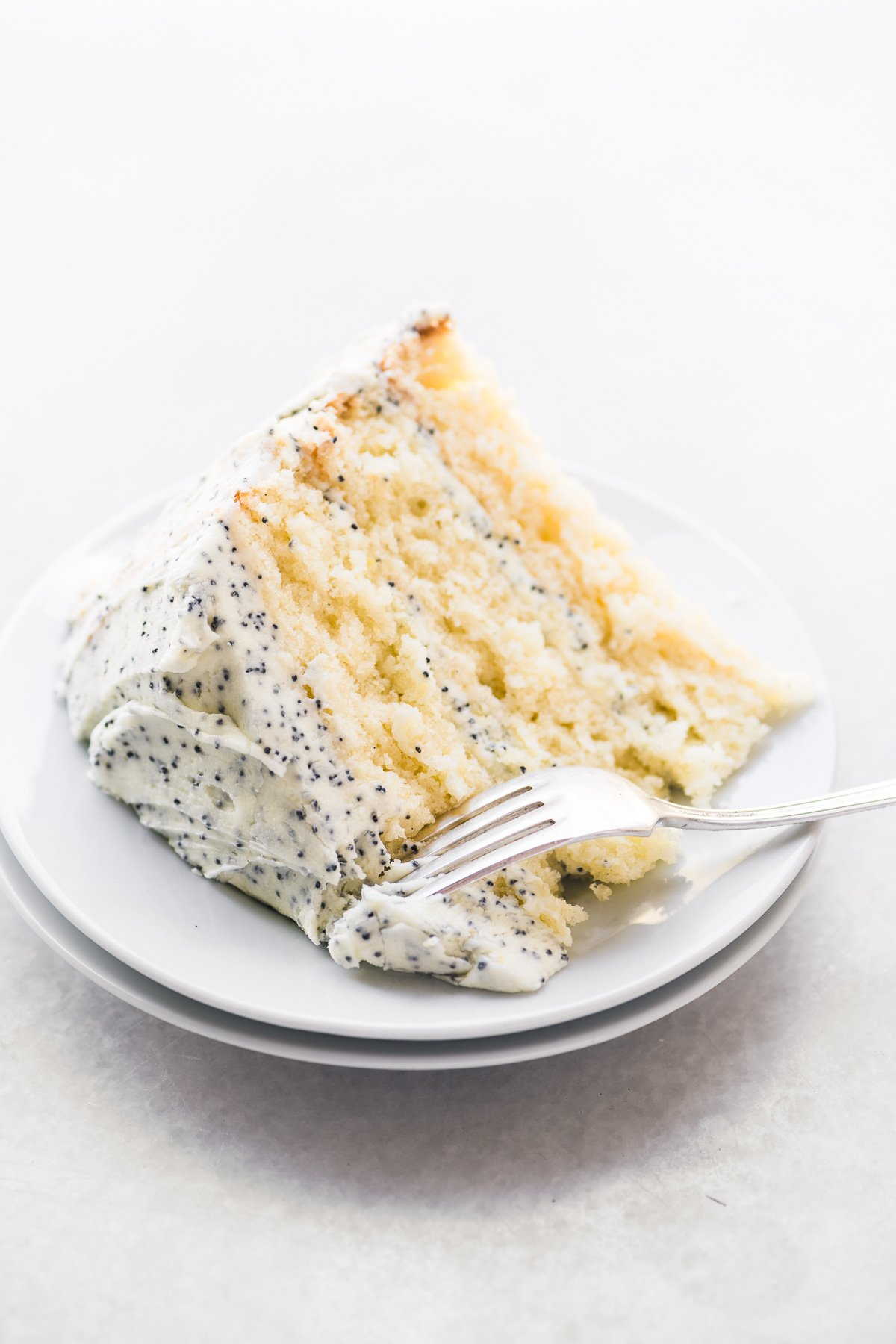 A slice of lemon layer cake with lemon poppy seed buttercream frosting, on a plate