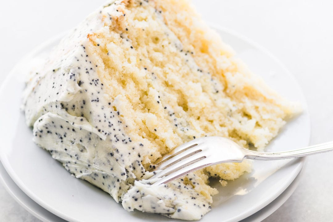 A slice of lemon cake with lemon poppy seed buttercream on a small plate with fork