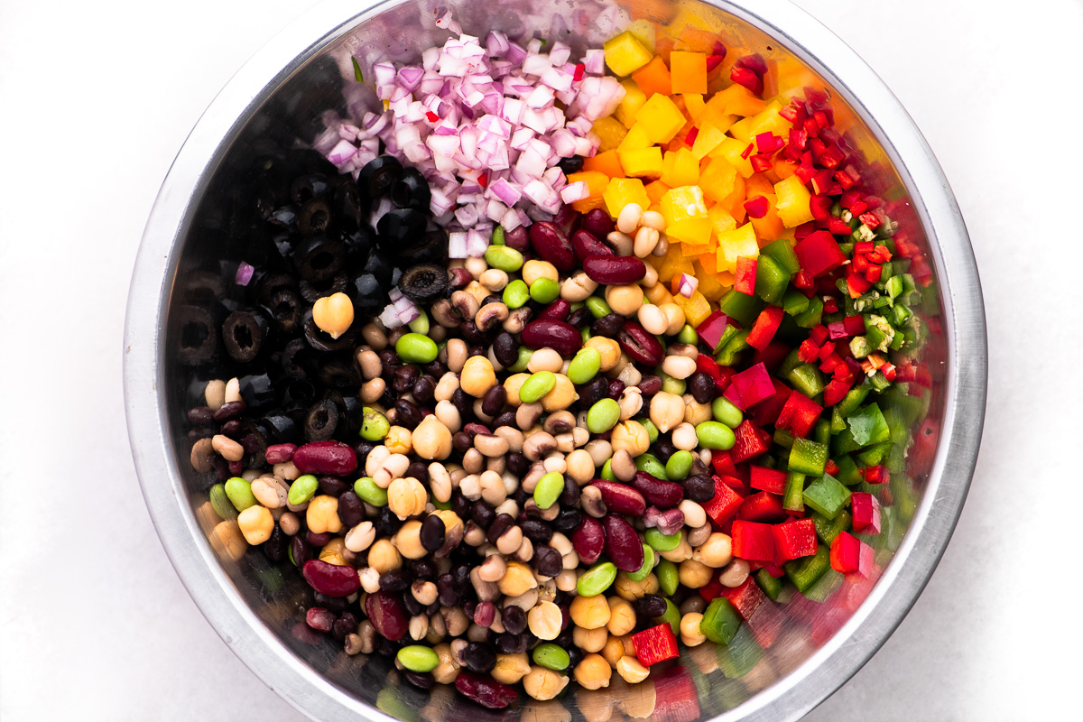 Ingredients for a rainbow bean salad in a metal mixing bowl
