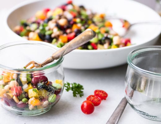 spponing rainbow bean salad into glass bowls