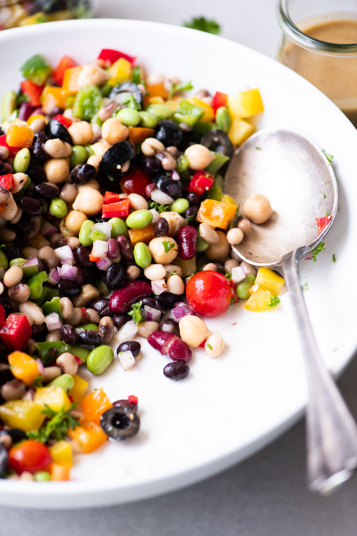 a bowl of rainbow bean salad with large serving spoon