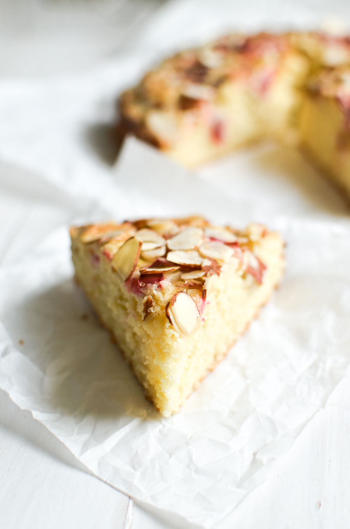 A slice of rhubarb cake on a piece of parchment paper