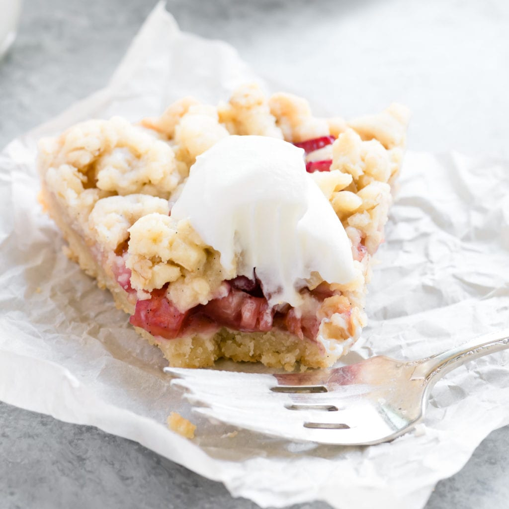 a slice of rhubarb shortbread crumble tart with whipped cream