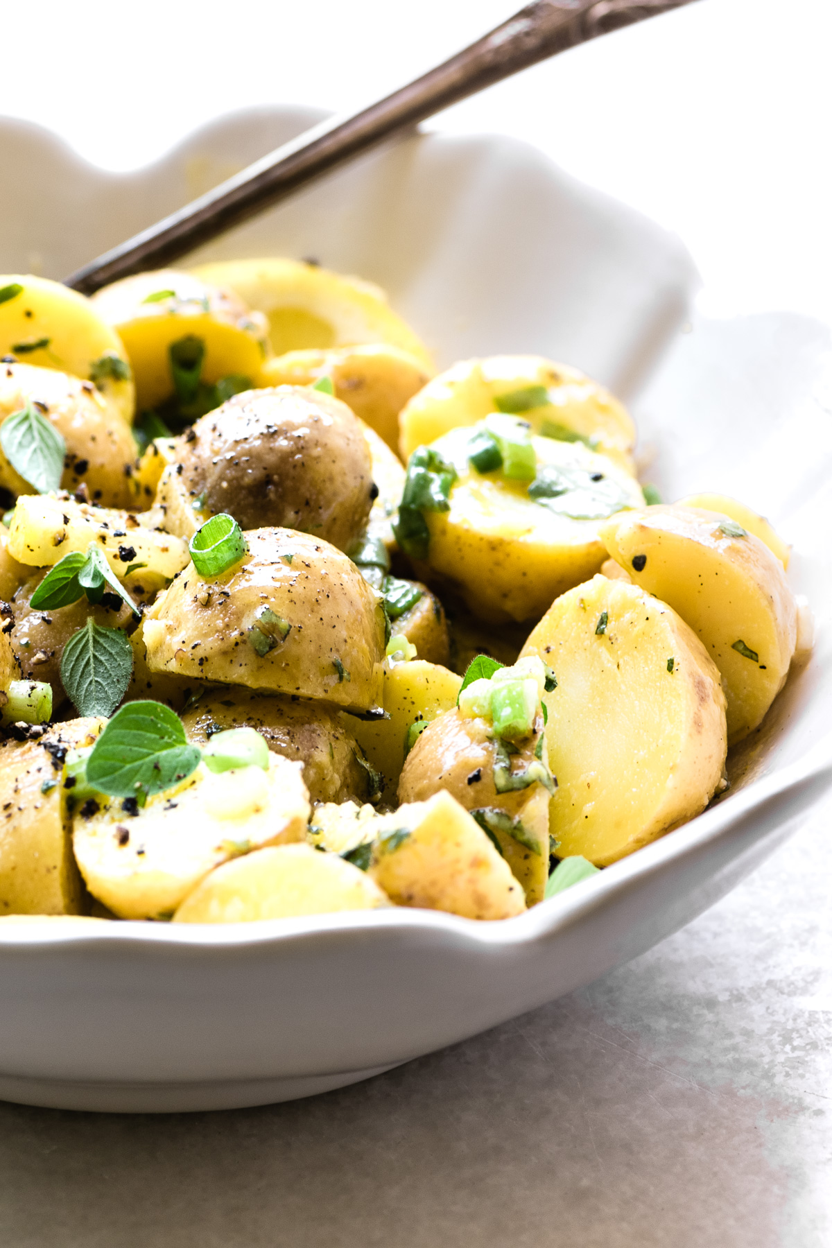 Greek Lemon Potato Salad in a white serving bowl