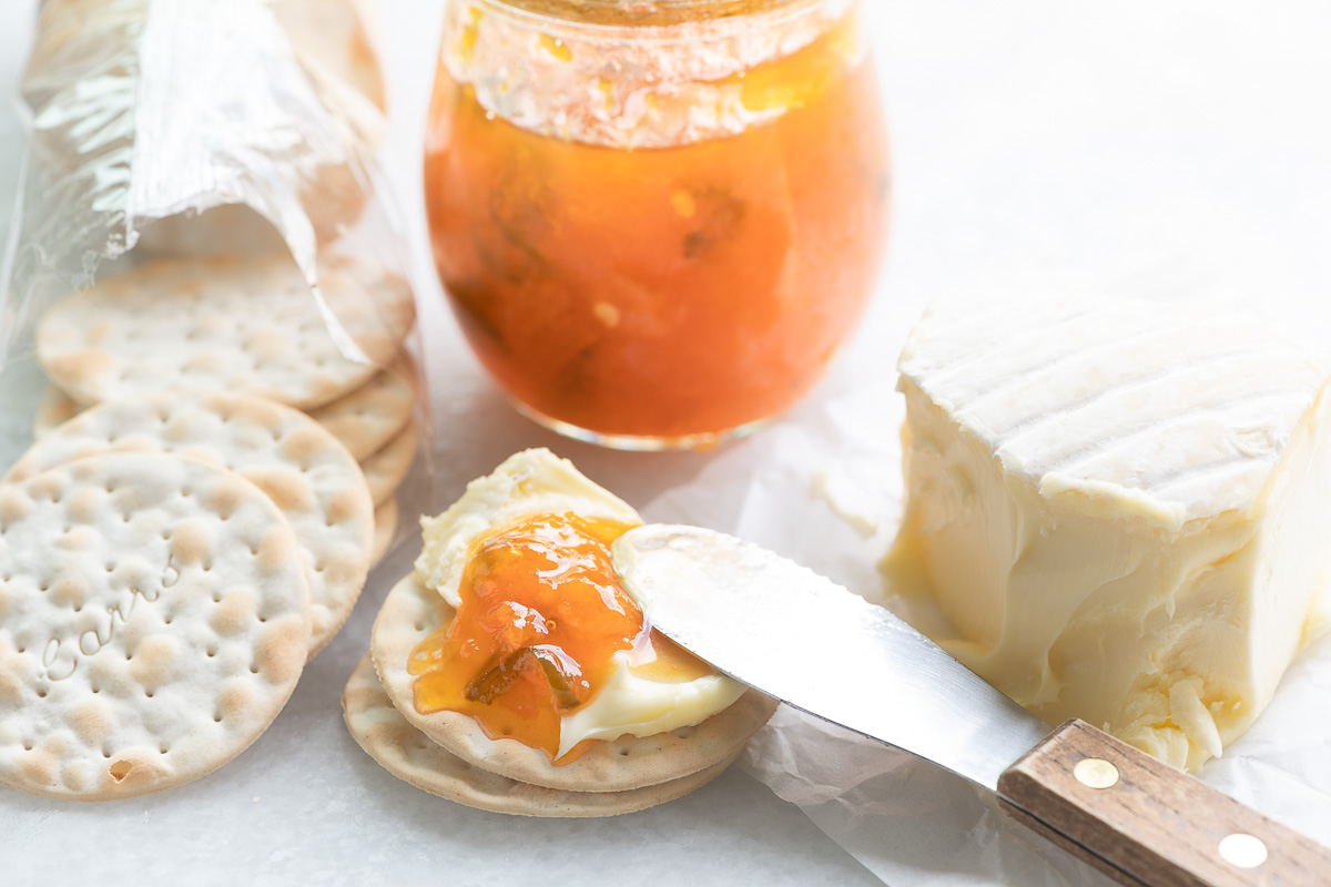 apricot jalapeño jam with cheese and crackers on a white marble surface