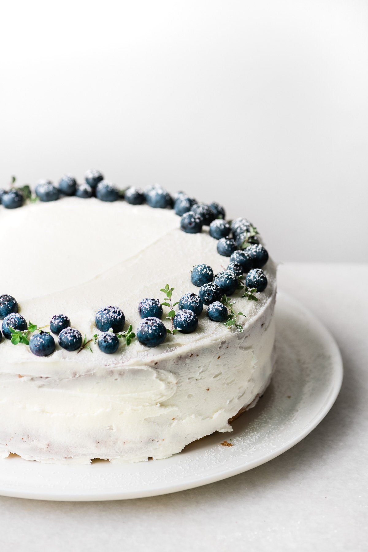 A blueberry lemon layer cake topped with fresh blueberries