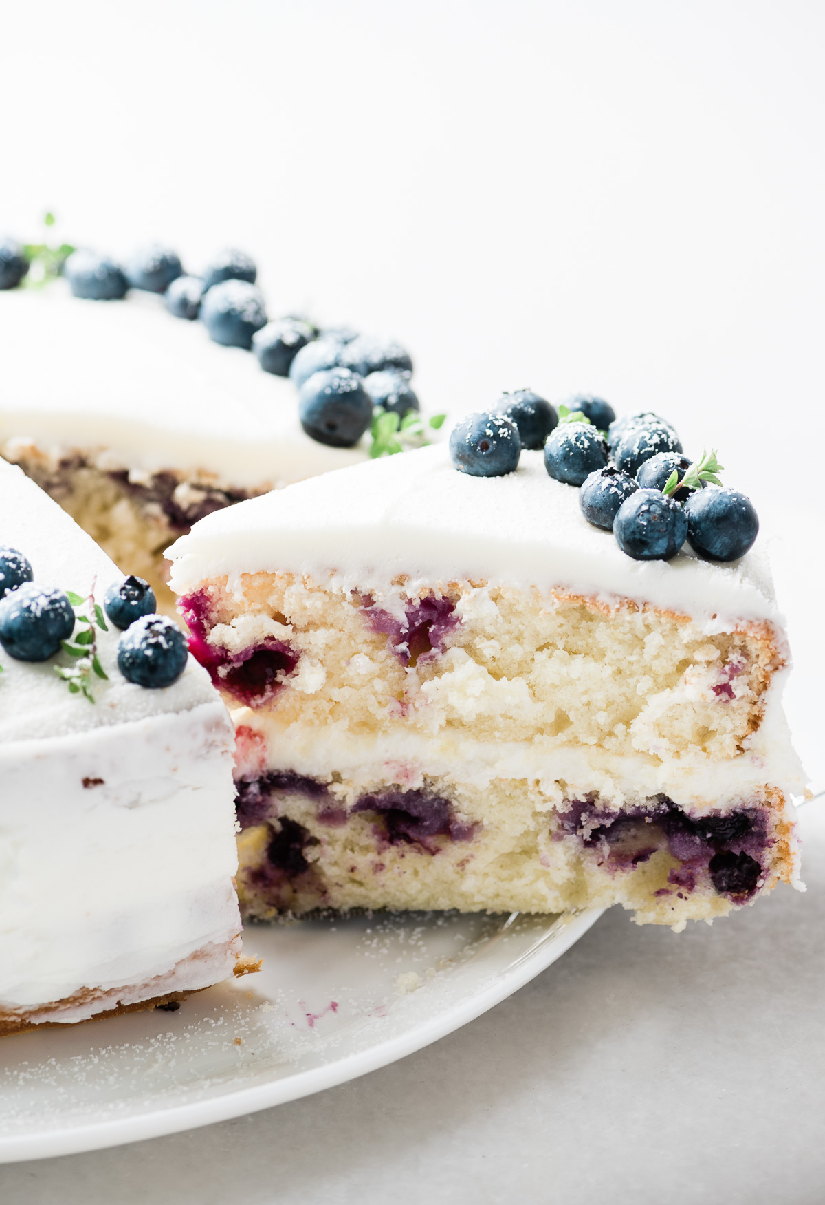 Removing a slice from a Blueberry Lemon Layer Cake