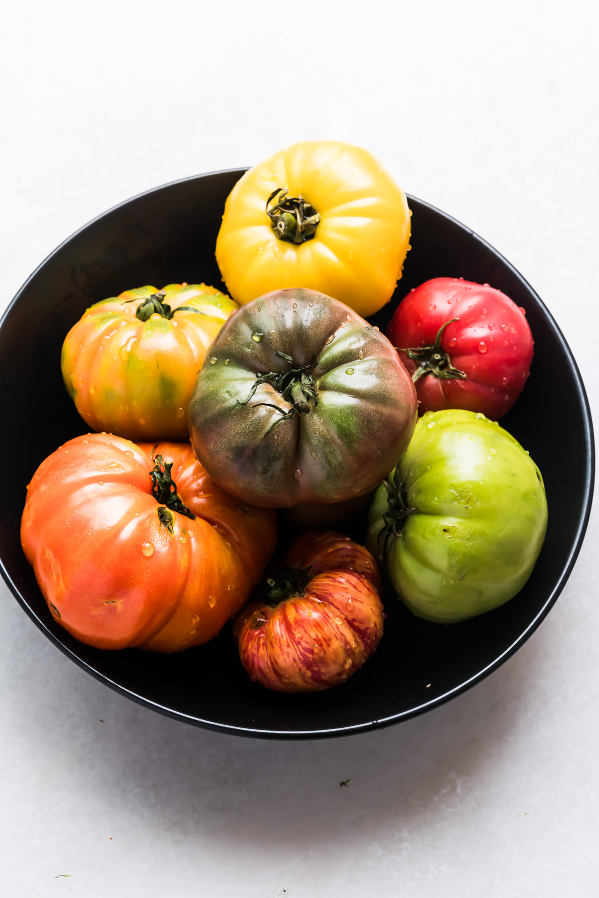 Assorted heirloom tomatoes in a black bowl