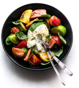 Burrata Caprese Salad in a black bowl with forks