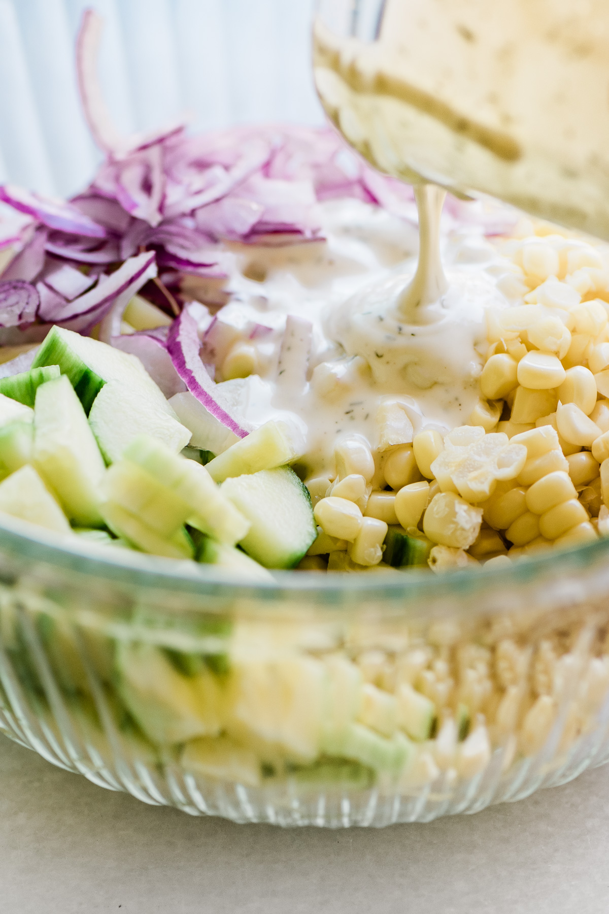 Pouring dressing on a corn and cucumber salad