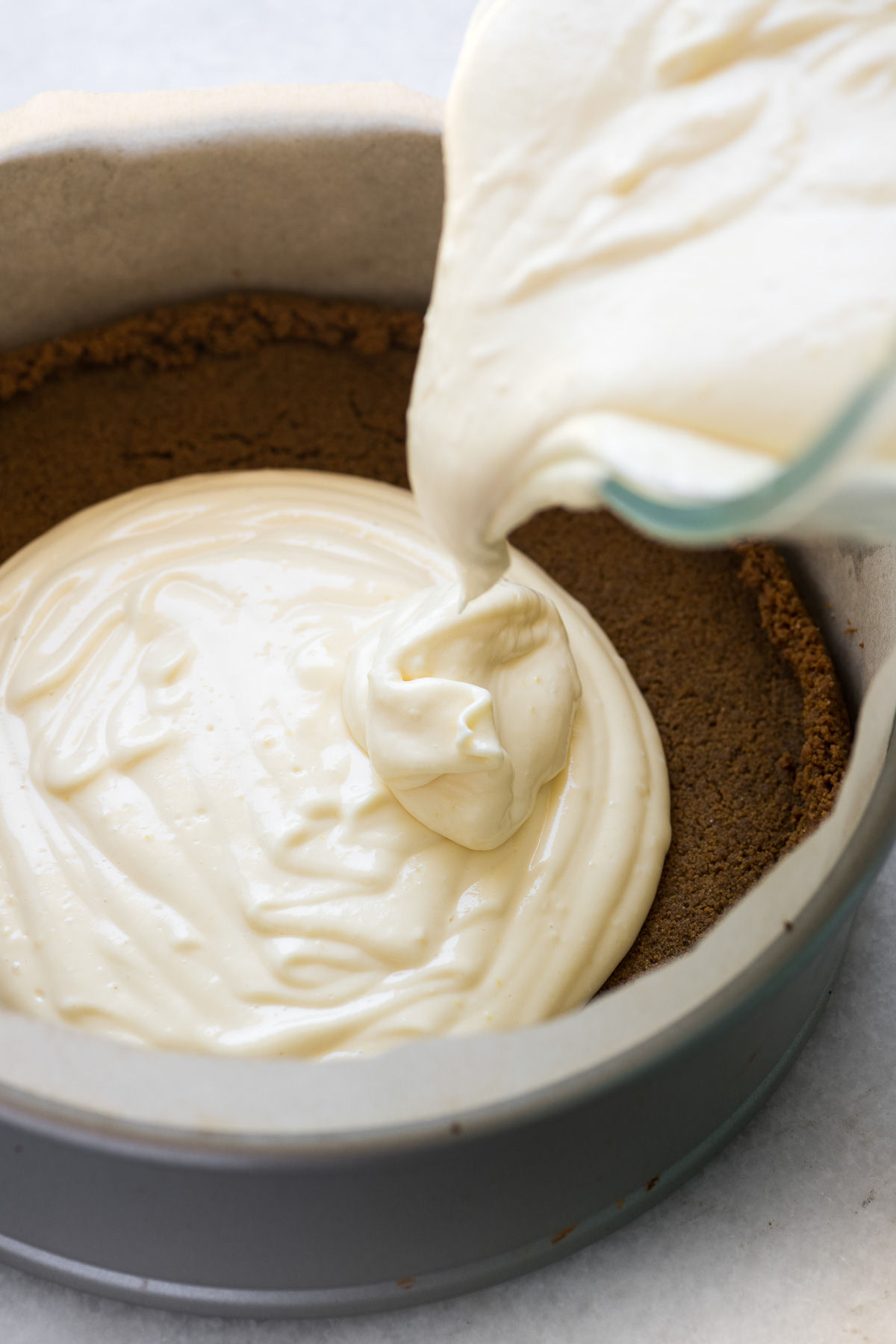 Pouring lemon cheesecake filling into the gingersnap crust