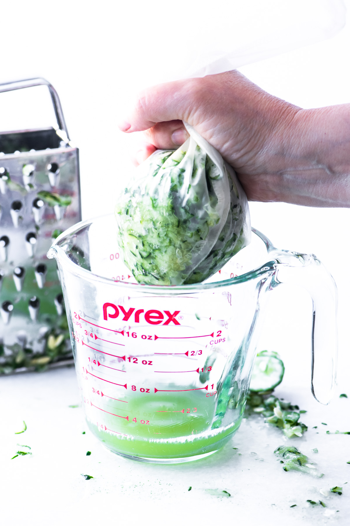 Squeezing excess moisture from shredded cucumber for homemade tzatziki dip