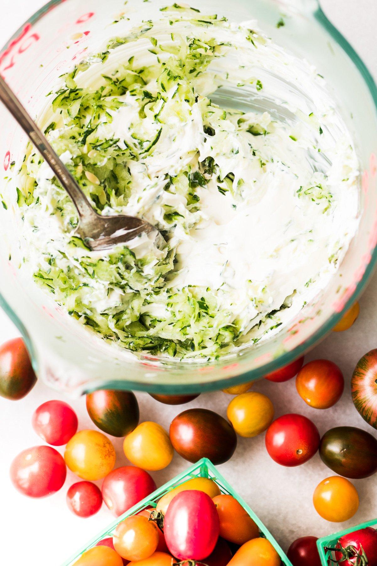 Making tzatziki dip with yogurt and shredded cucumber