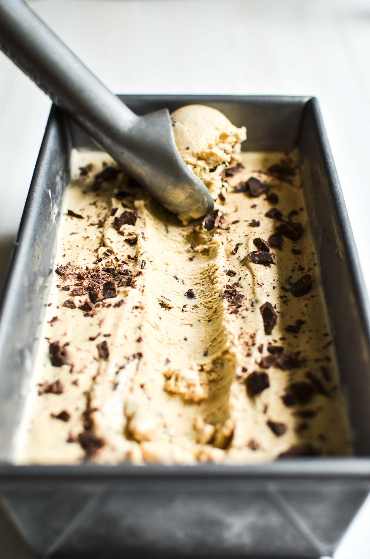 Chocolate chip cookie dough ice cream being scooped out of a loaf pan.
