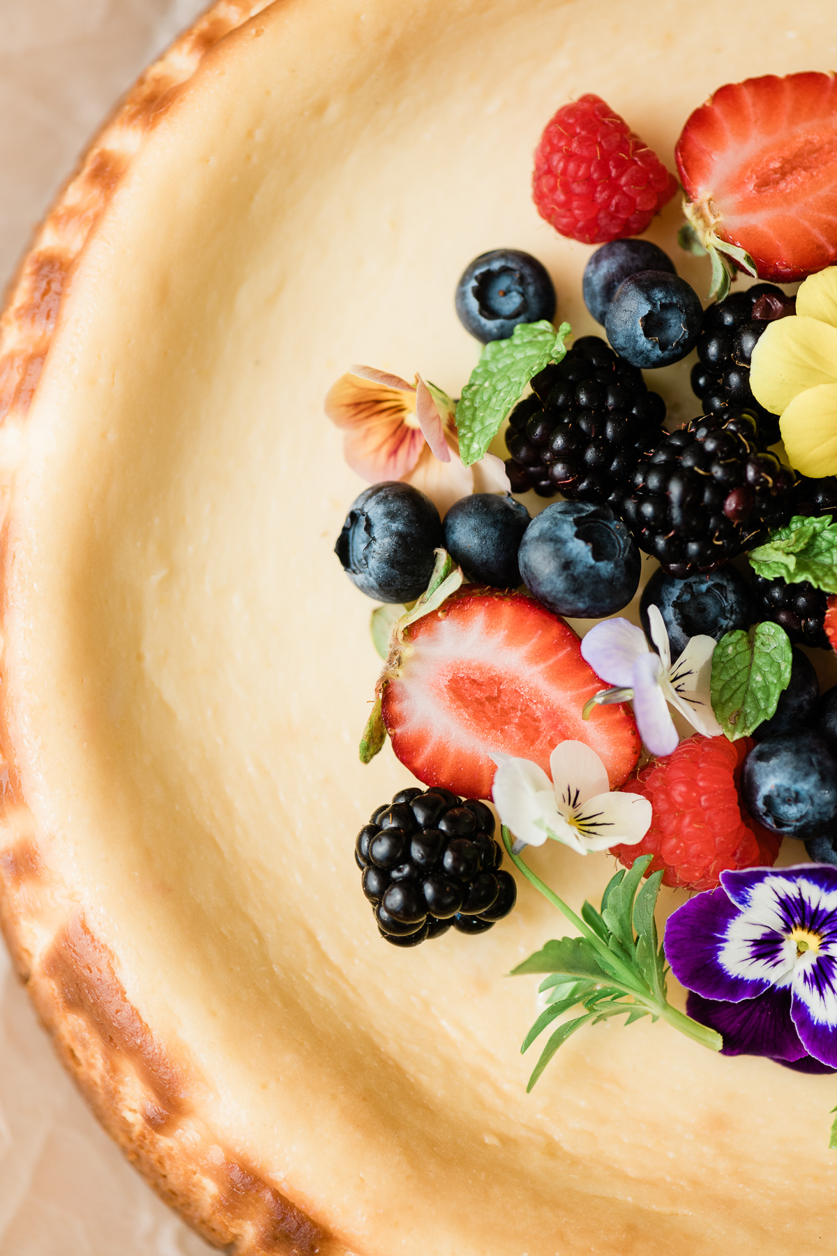 Lemon cheesecake topped with berries and edible flowers