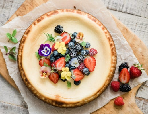 Classic Lemon Cheesecake topped with fresh berries and edible flowers