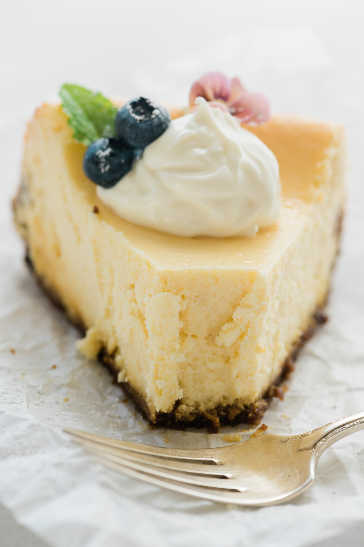 A slice of lemon cheesecake topped with whipped yogurt