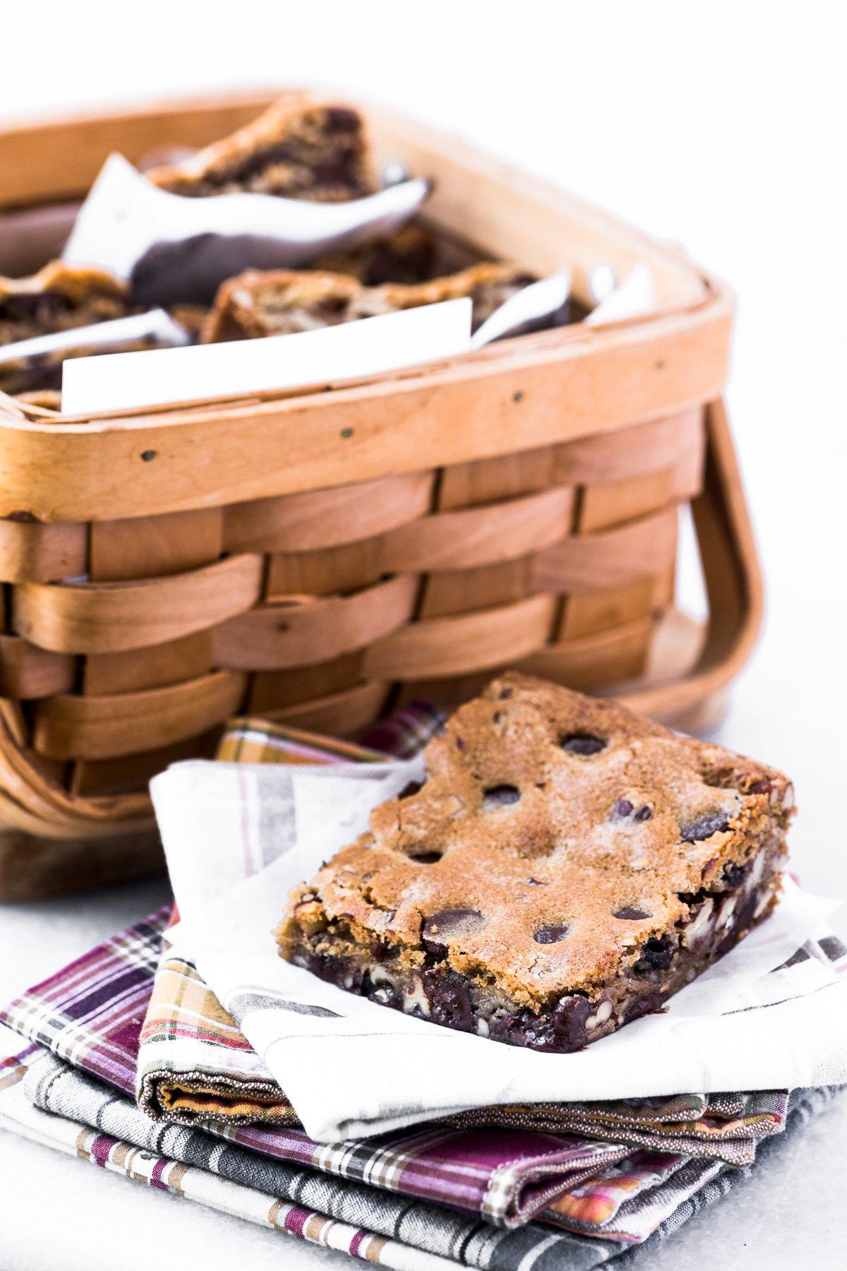 dark chocolate pecan blondie on a stack of napkins