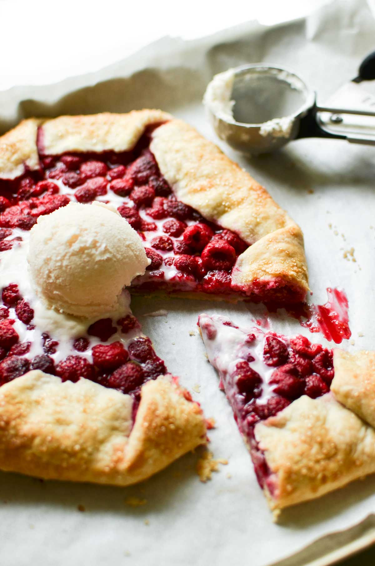 Fresh raspberry galette on a baking sheet with ice cream scoop