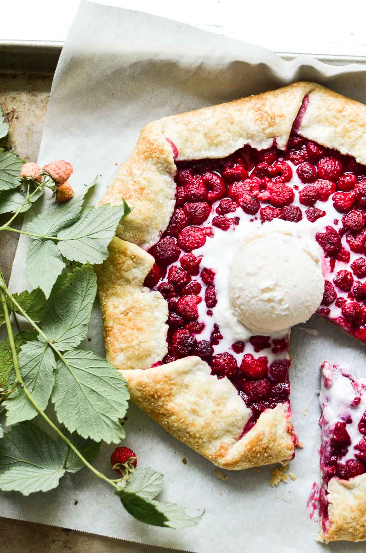 a fresh raspberry galette on a baking sheet