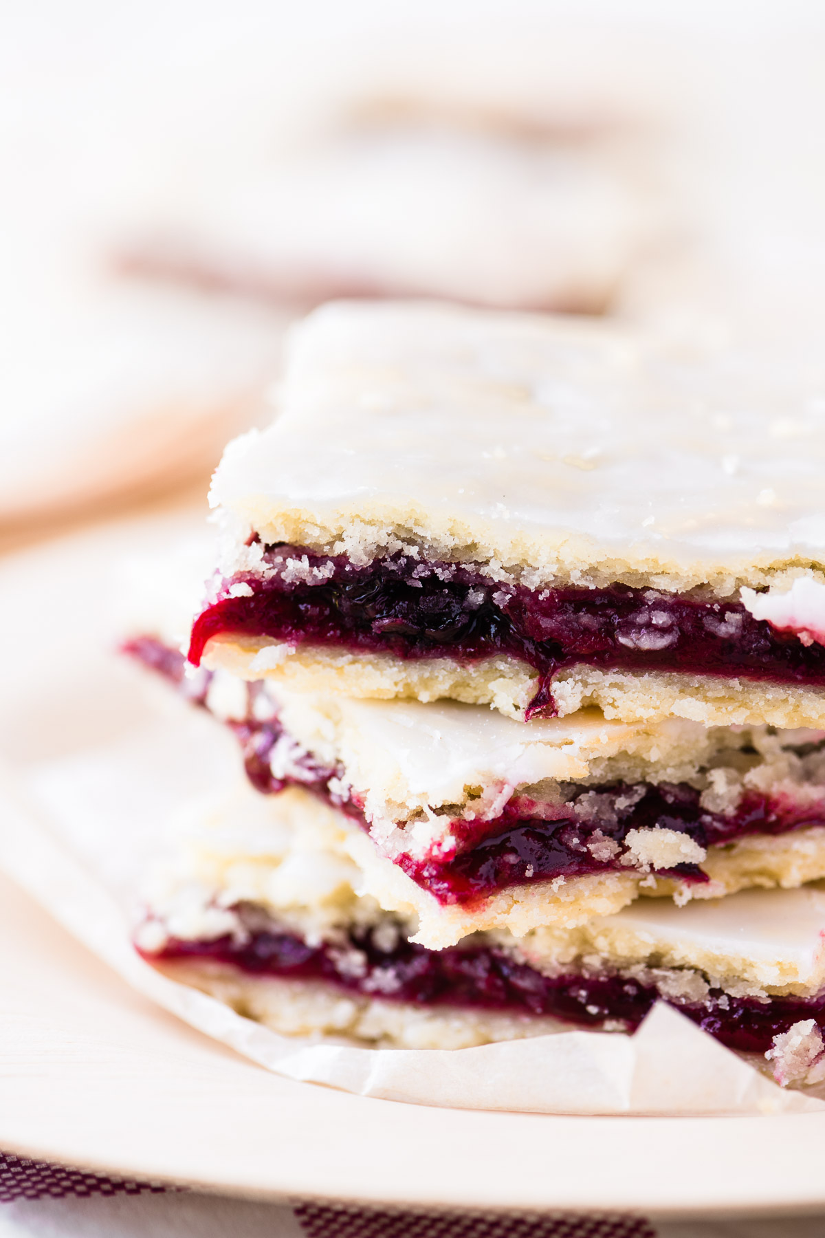 a stack of blackberry slab pie bars on parchment paper