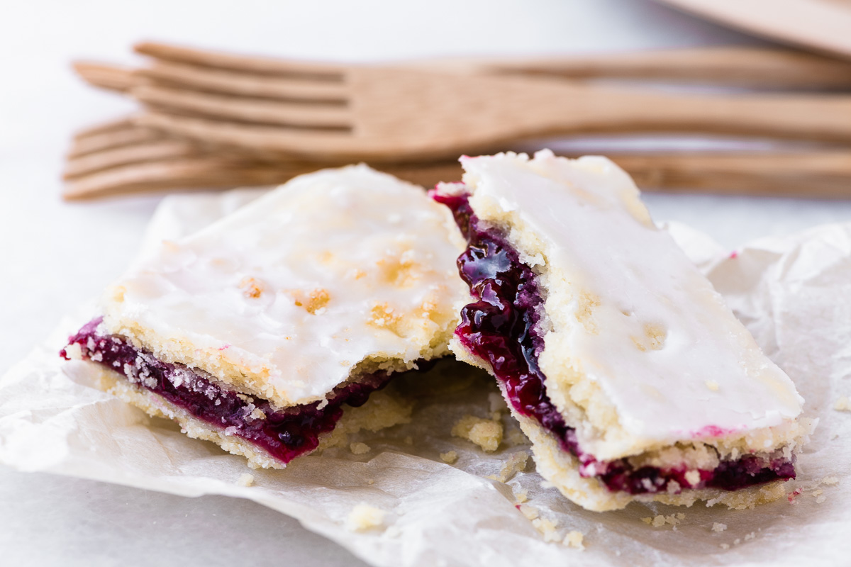 a blackberry slab pie bar on a napkin with forks
