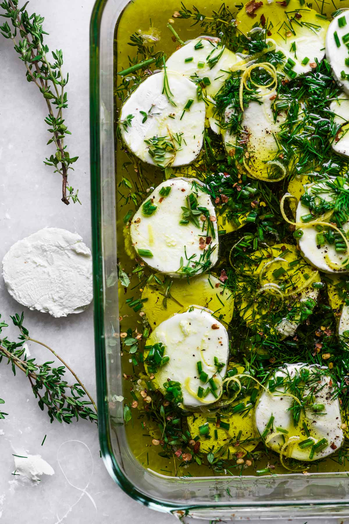 goat cheese slices marinating in oil and herbs
