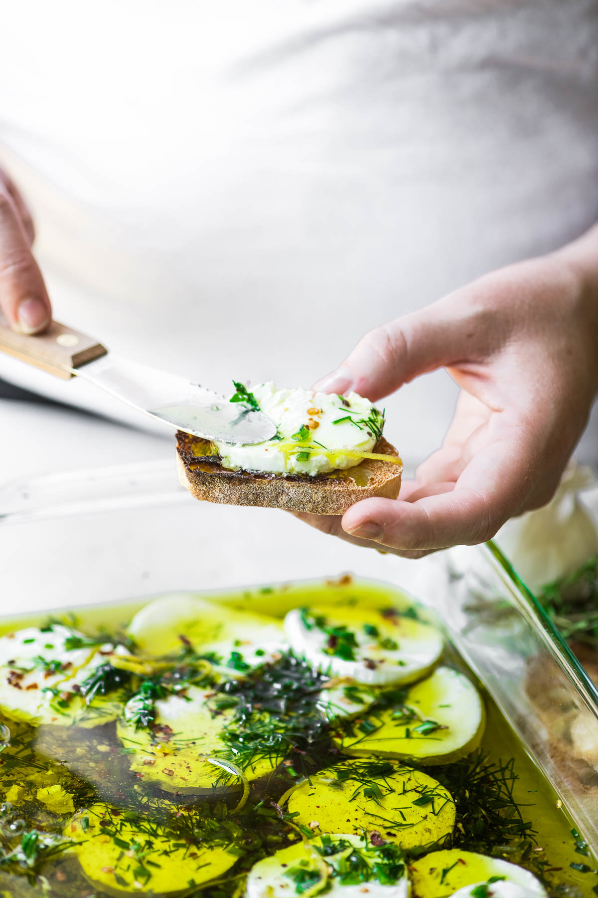 spreading herb marinated goat cheese on a slice of bread