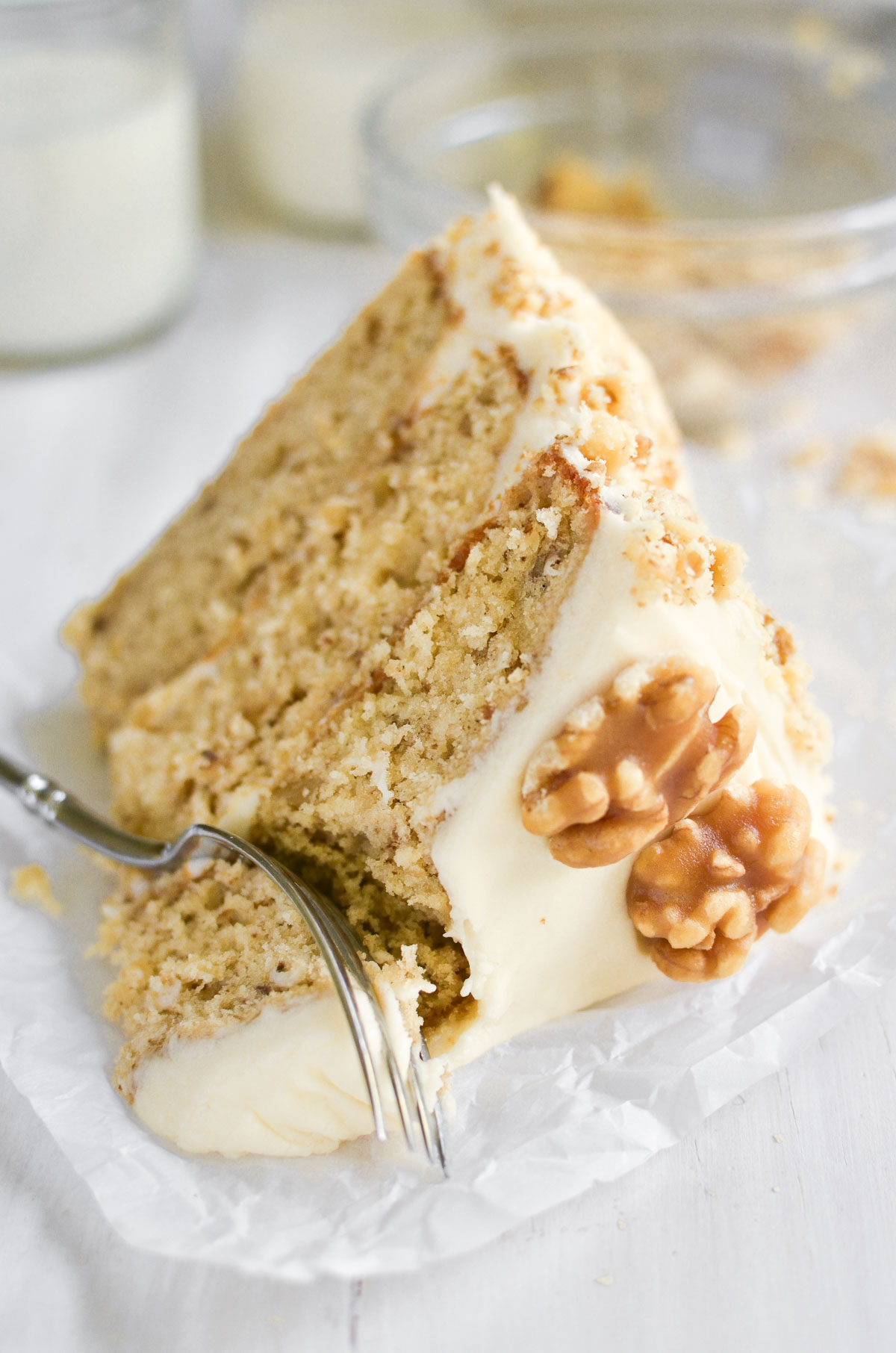 a slice of maple walnut cake with maple cream cheese frosting