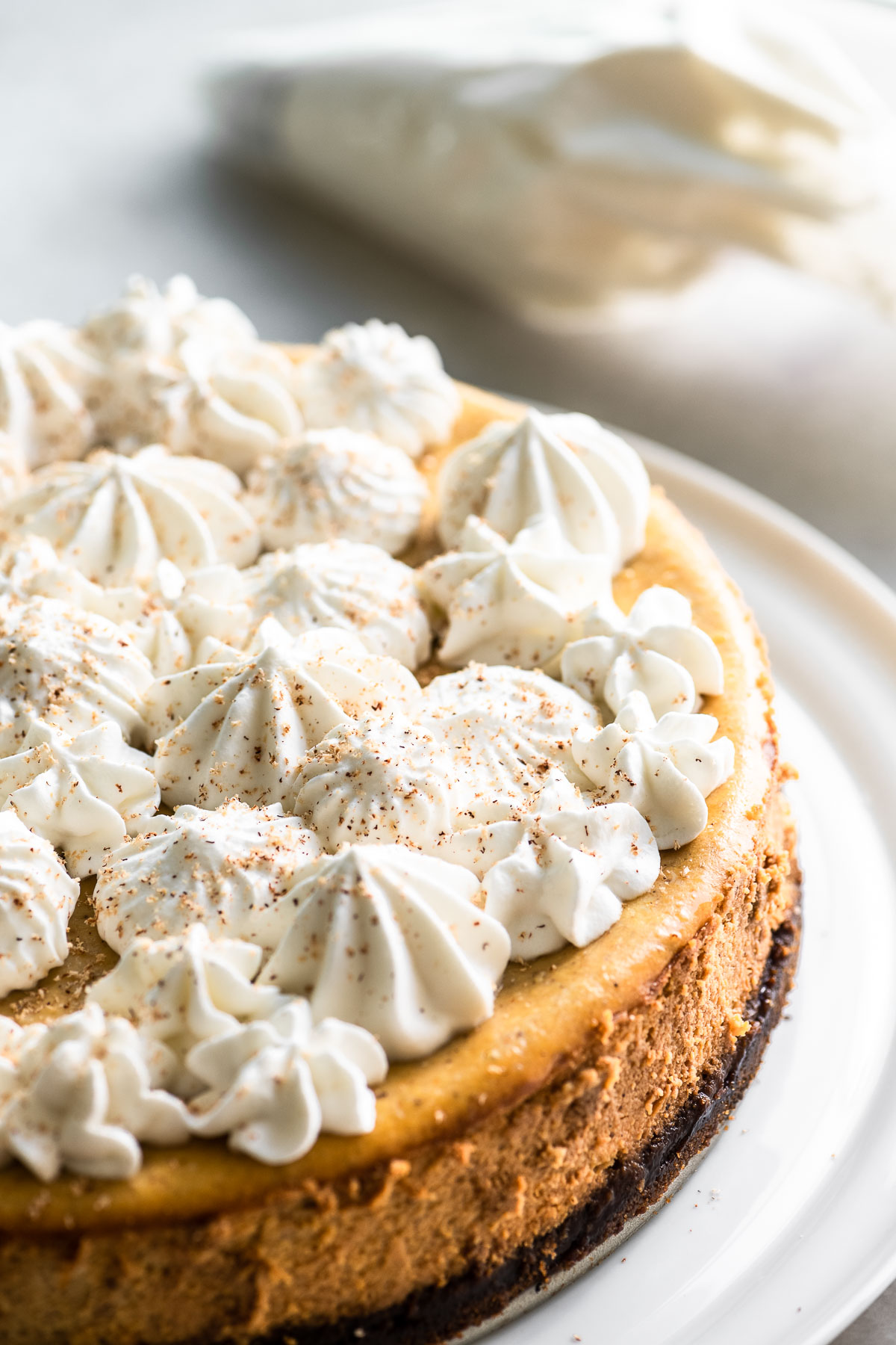pumpkin cheesecake with whipped cream and nutmeg
