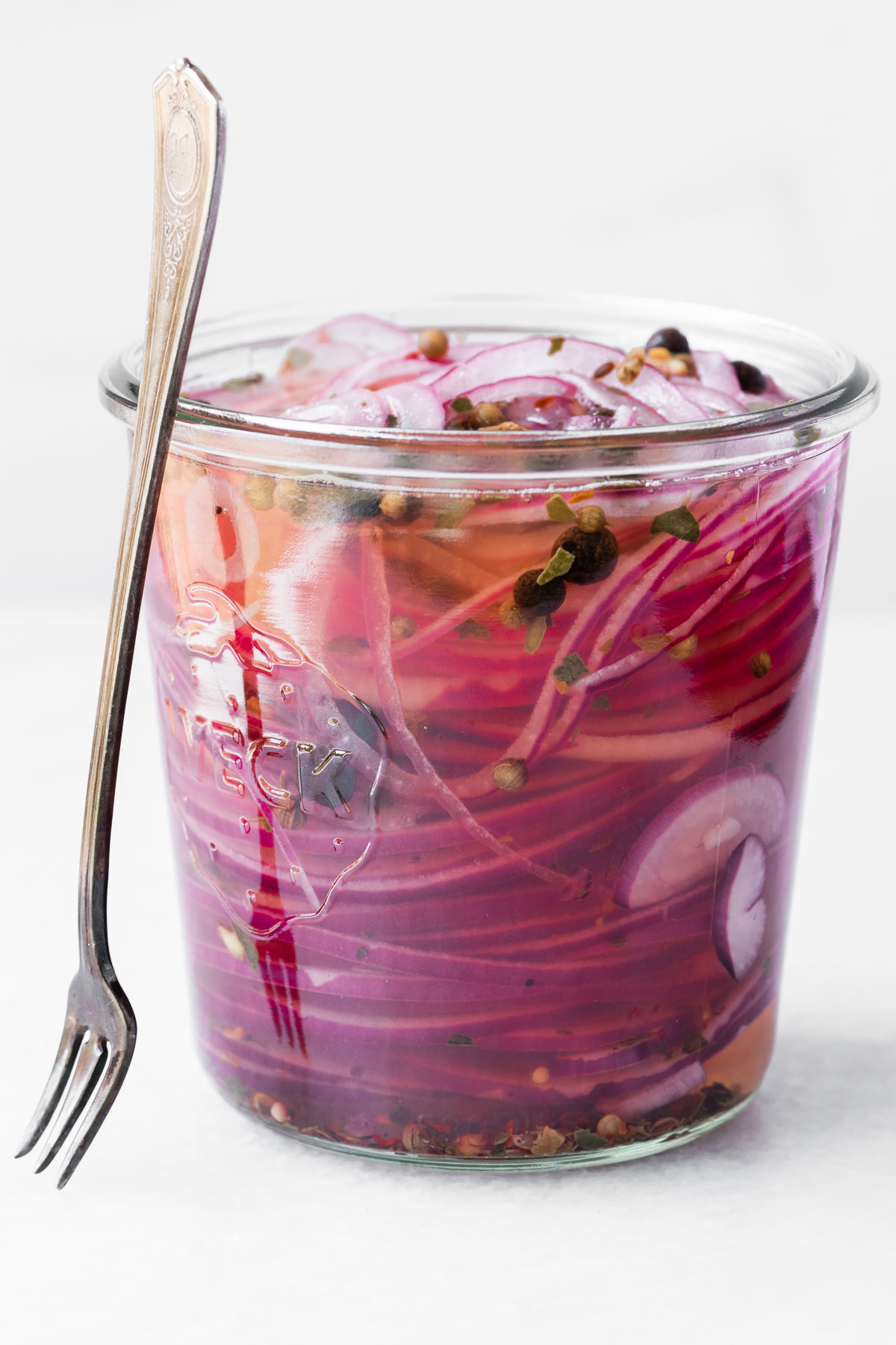 quick pickled red onions in a jar with fork