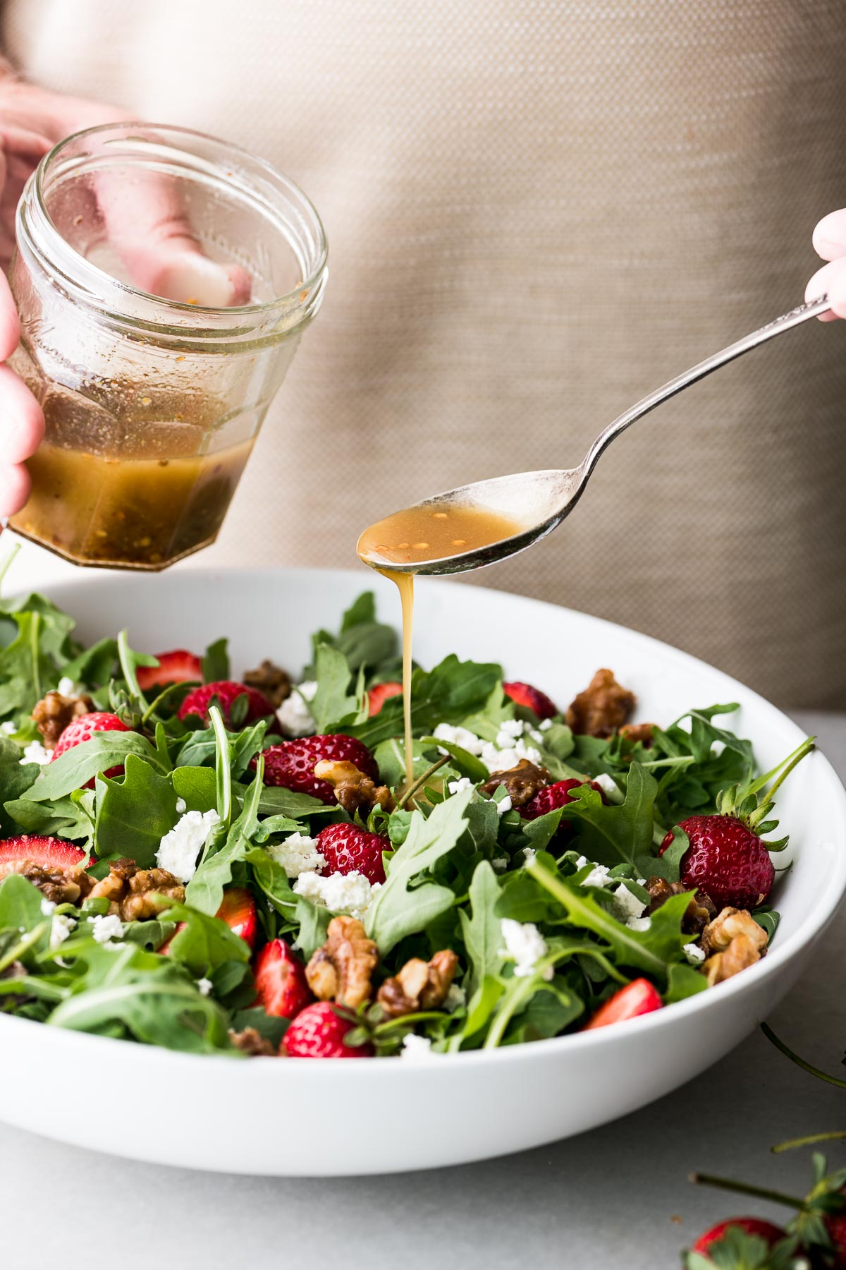 Dressing a strawberry arugula salad