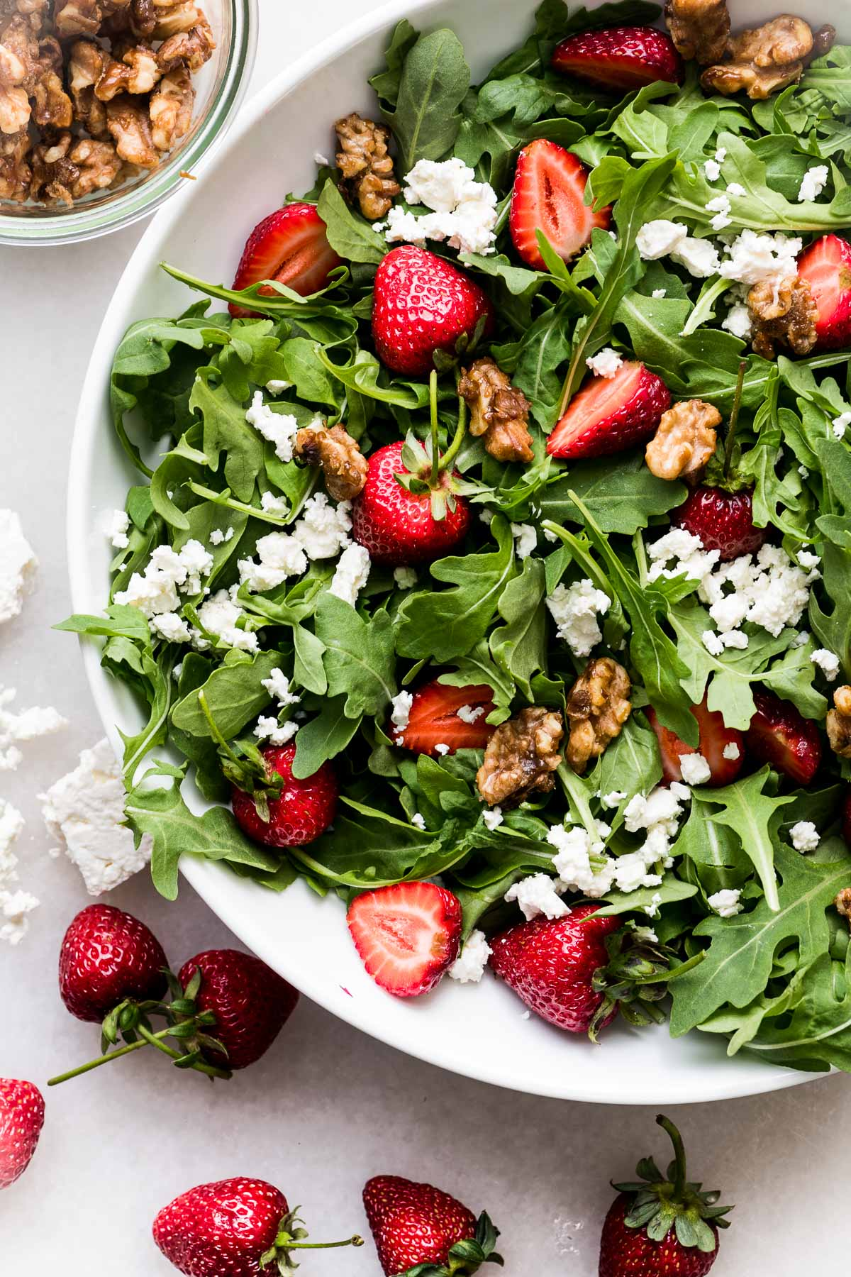 strawberry arugula salad in a white bowl