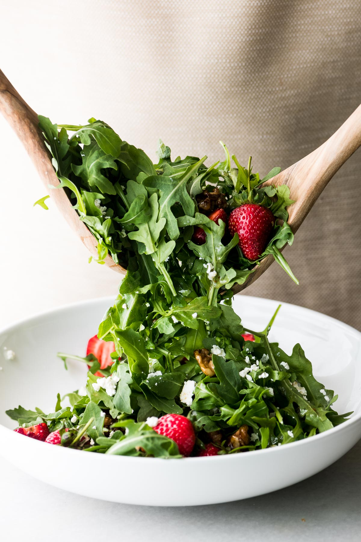 tossing a summer strawberry salad