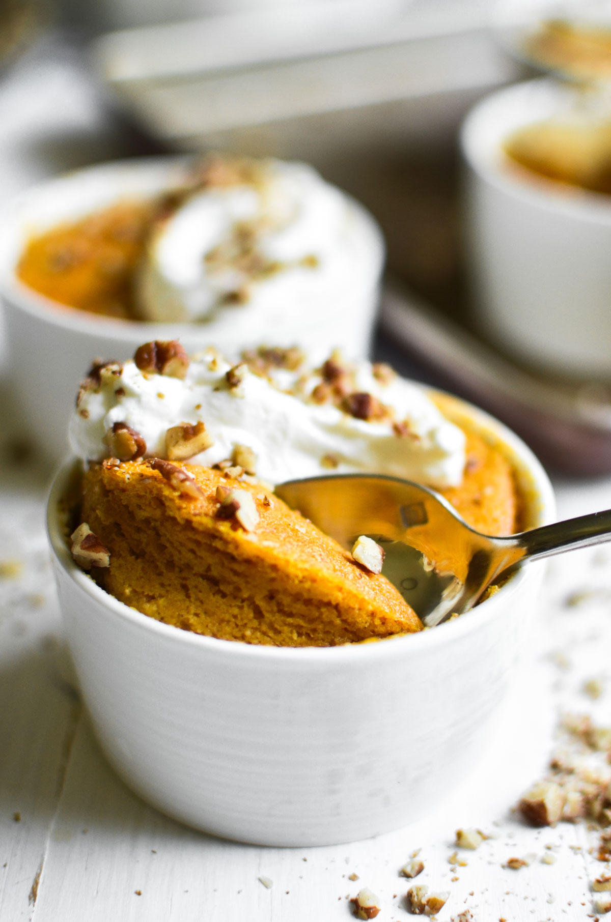 pumpkin pudding cake in a bowl with whipped cream