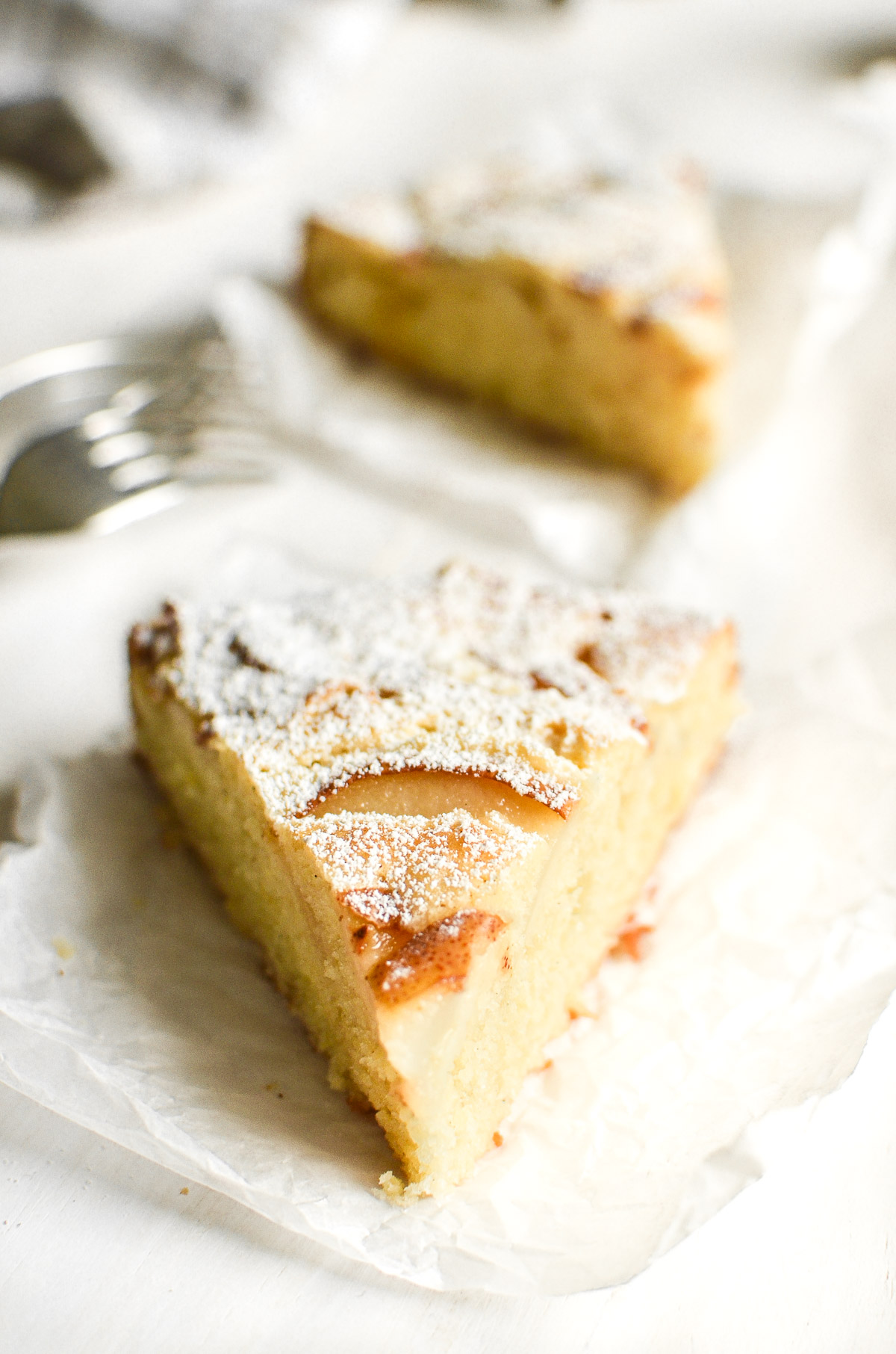 A slice of fresh ginger and pear cake, with another slice and forks in the background.