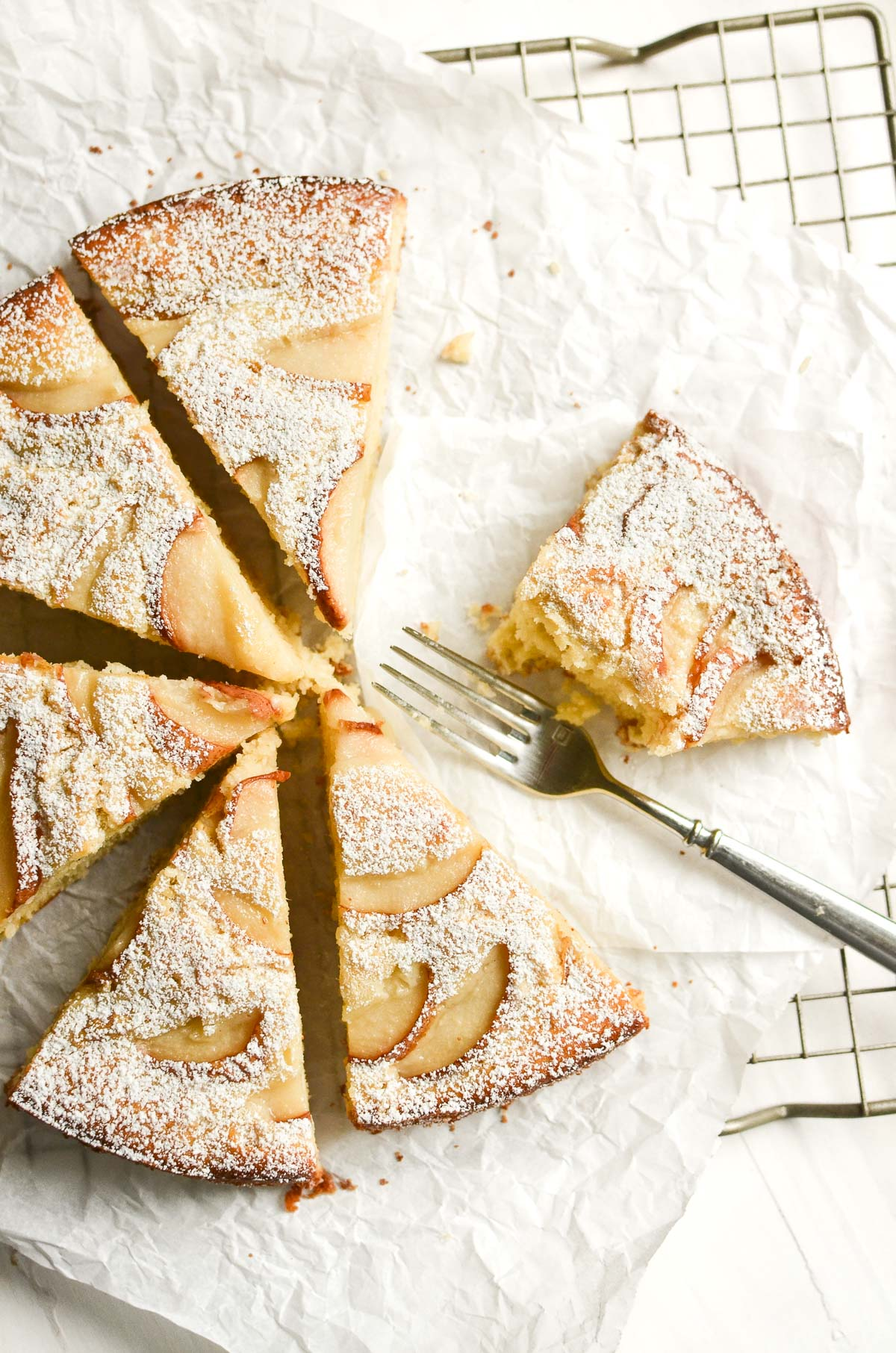 Fresh Ginger and Pear Cake on a baking rack, sliced into pieces.
