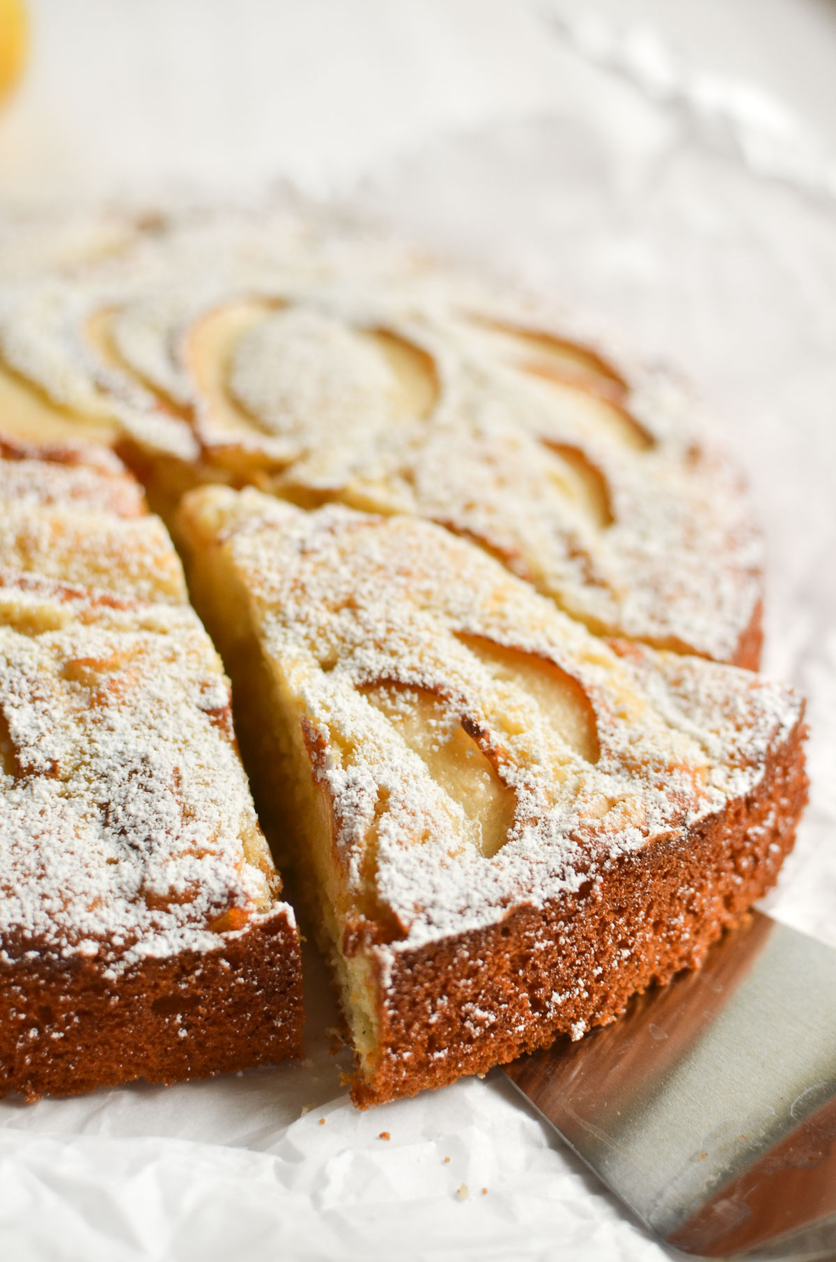 Fresh Ginger and Pear Cake with a slice being taken out.