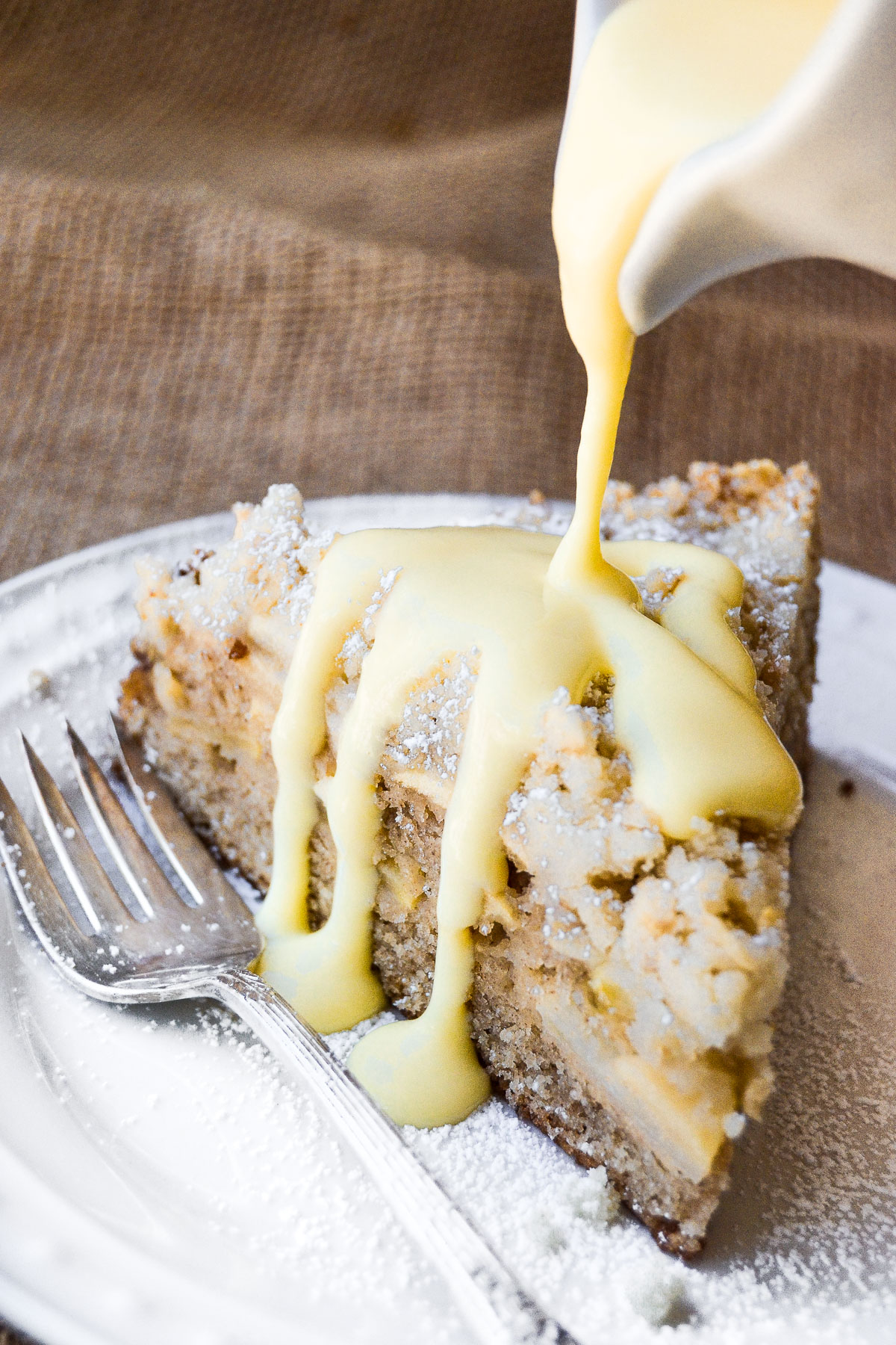 pouring custard sauce on a slice of Irish Apple Cake