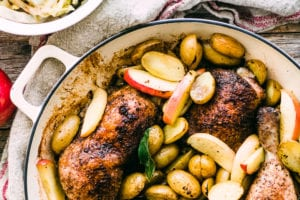 roast chicken with potatoes, apples, and brown cabbage in a cast iron pot