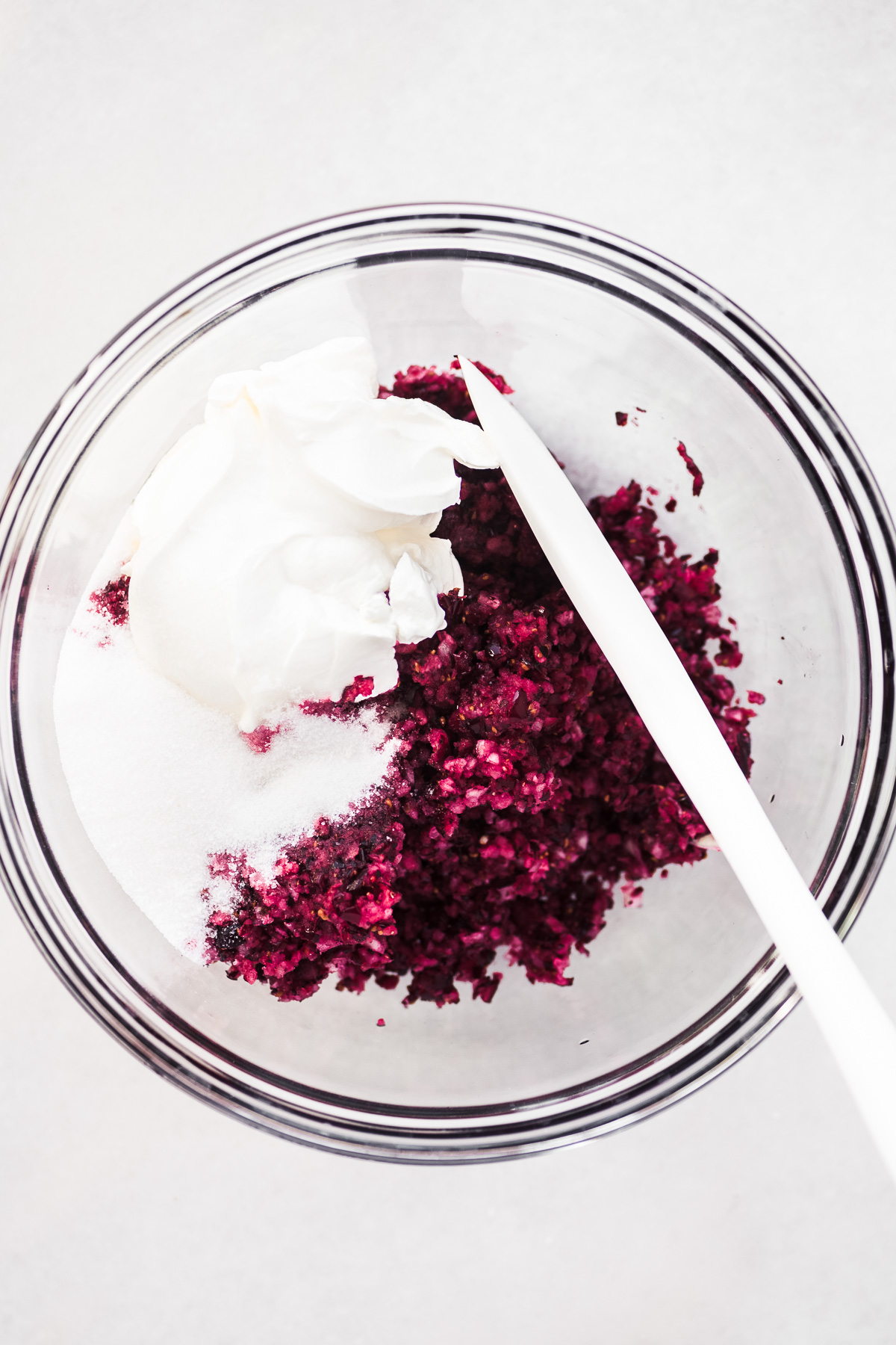 Mixing up cranberry relish in a glass bowl